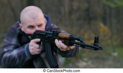 Insurgent with a gun aiming - Bald man with AK aiming