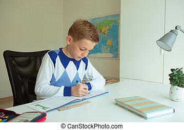 Intelligent boy makes homework in his room