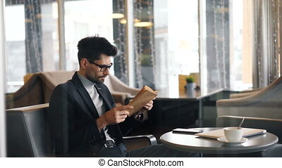 Intelligent businessman reading book turning pages sitting...