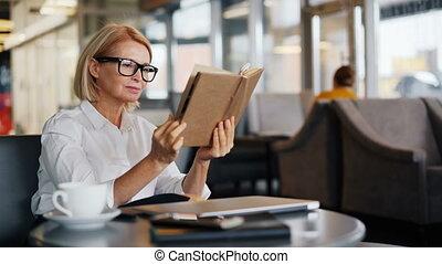 Intelligent businesswoman enjoying book reading in cafe...