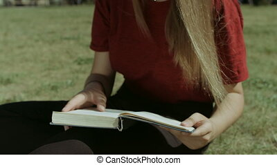 Intelligent girl reading a book outdoors - Midsection of...