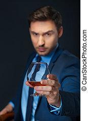 Intelligent man drinking cognac