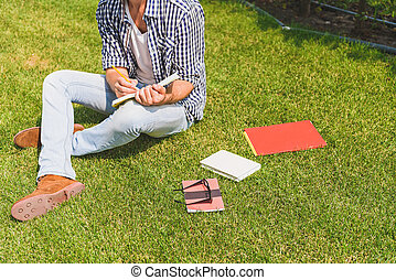 Intelligent young man making notes in park