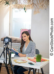 Intelligent young woman recording a video for blog