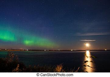 Intense Aurora borealis (northern lights) in moon lit night being mirrored on lake