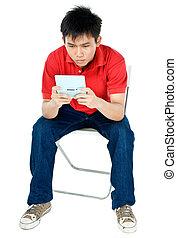 Intense Gaming - asian teen playing an electronic game