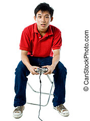 Young teenage guy wearing red shirt, blue jeans, playing a hand held game