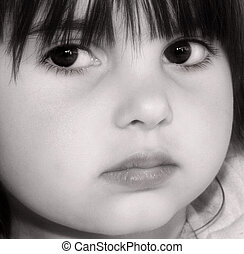 The face of a young girl with an intense look on her face. In monochrome.