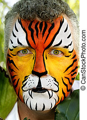 A man with piercing eyes, painted like a tiger.