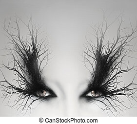 Two artistic female eyes with decoration of branches around them as a make up in a light grey background