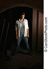 Intense man standing in dark - A intense man standing in the...