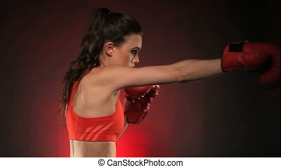 Intense woman boxer throwing punches - Side view of...