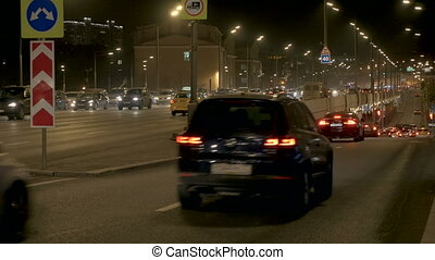 Intensive traffic of cars, along city streets. On the...