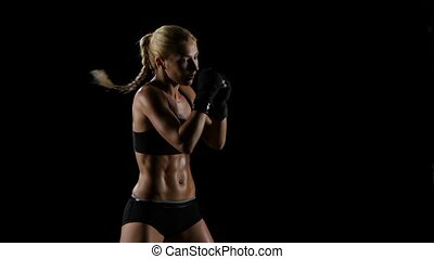 Intensive training boxer girl in a studio setting. Slow motion