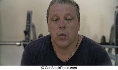 Slow motion of a man having a rest after intensive workout. He is tired and wiping sweat with a towel
