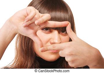 Intent gaze through finger frame of young brunette woman