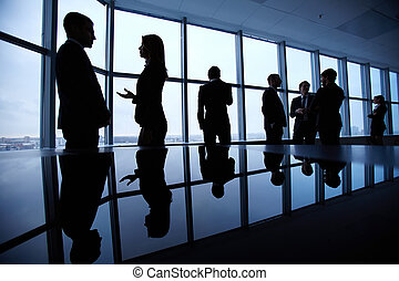 Interacting in office - Group of colleagues standing against...