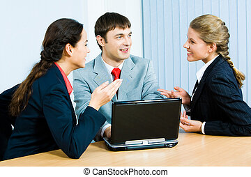 Photo of business ladies and businessman sitting at the table and speaking during business meeting in the office