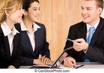 Portrait of happy businessman speaking to his colleagues at meeting while they listening to him with smiles