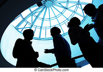 Interaction - Silhouette of business people interacting with...