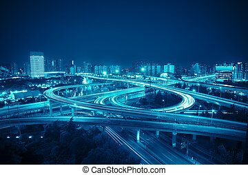 interchange in shanghai at night, clover stack type overpass with blue tone