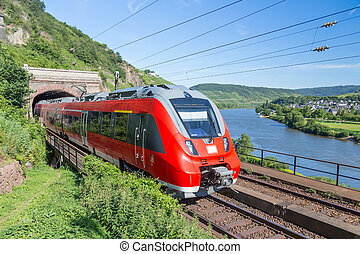 Intercity train leaving a tunnel near the river Moselle in...