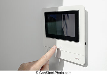 Intercom in home interior and a hand ready to open the door button. House Security system. Copy space