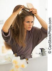 interessado, mulher jovem, penteando cabelo, em, banheiro