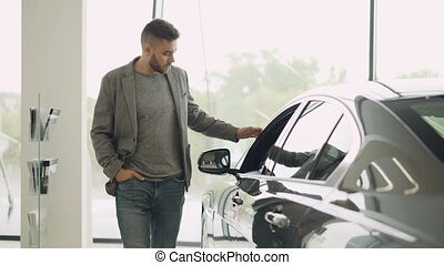 Interested customer is inspecting beautiful automobile in...