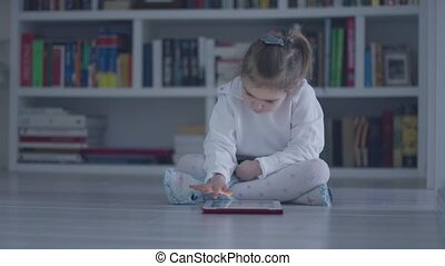 Interested girl with tablet on floor - Casual little girl in...