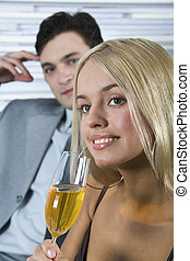 Interested glance - Smiling cute blond woman drinking ...