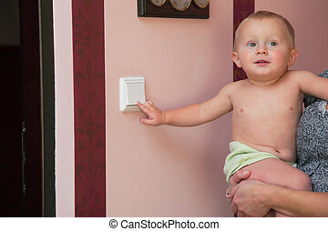 interested little boy on mother hands turning off the light-switch