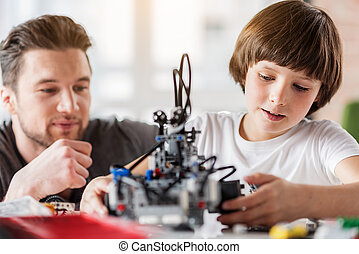 Concentrated boy is making robot. Curious adult man is squatting behind and looking at child with proudness
