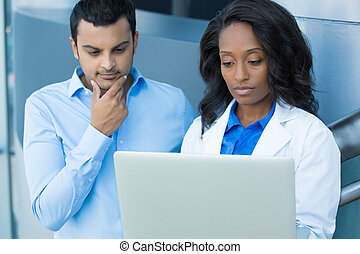 Closeup portrait of intellectual healthcare professional with white labcoat, looking at record, discussing findings with young patient, using digital technology, isolated hospital clinic background