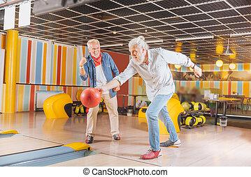 Joyful strong man throwing the bowling ball
