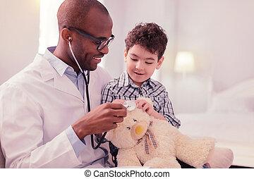Nice joyful man playing with his son