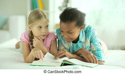 Girls reading the book and looking at pictures