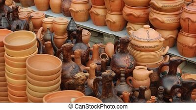 Interesting variety of decorative, terra cotta containers and cookware, displayed for sale at a public market in the Republic of Georgia. Video DCI 4k