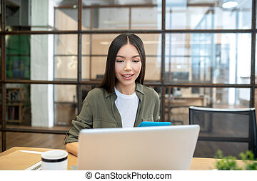 Long-haired brunette asian girl working in the office and looking excited