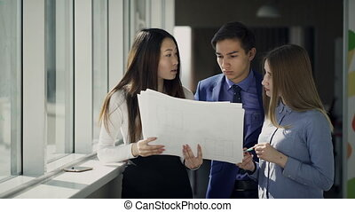 Interethnic group discuss in the office information in the document. People with an eastern and European appearance hold a pile of papers