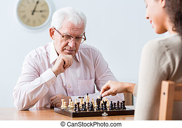 Intergenerational duel at chess - Senior smart man playing...
