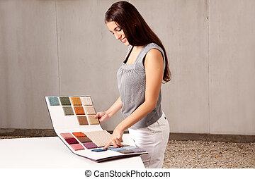 Interior Architect Choosing Rug Sample - A female interior...