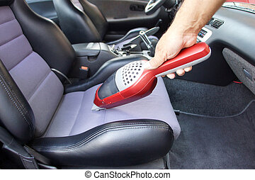 Interior car cleaning - Hand holding portable vacuum cleaner...