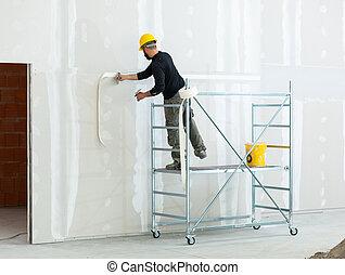 worker plastering gypsum board wall. - Interior construction...