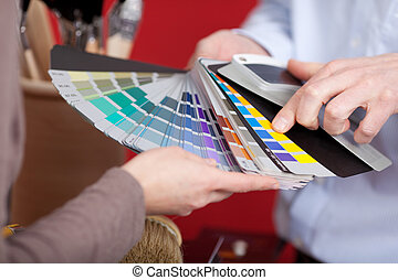 Interior decorator in a meeting with a client discussing various paint colours from a colourful set of swatches he is holding in his hand