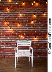 white chair against a background of a brick wall with a garland