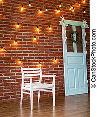 Interior design white chair against a background of a brick wall with a garland