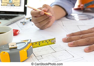 Interior designer discussing data and digital tablet and computer laptop with business document and graphics design diagram on wooden desk as concept
