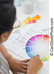 Interior designer looking at colour wheel at her desk in...