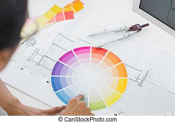 Interior designer looking at colour wheel at desk